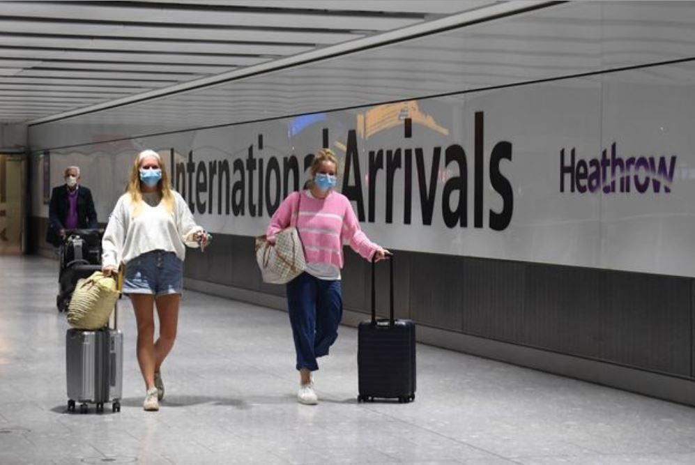مسافرتين يرتديان الواقي الصحي بمطار هيثرو